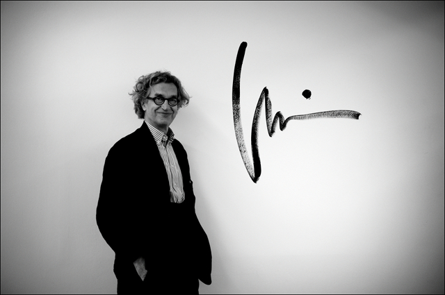 Wim Wenders posing in front of his signature